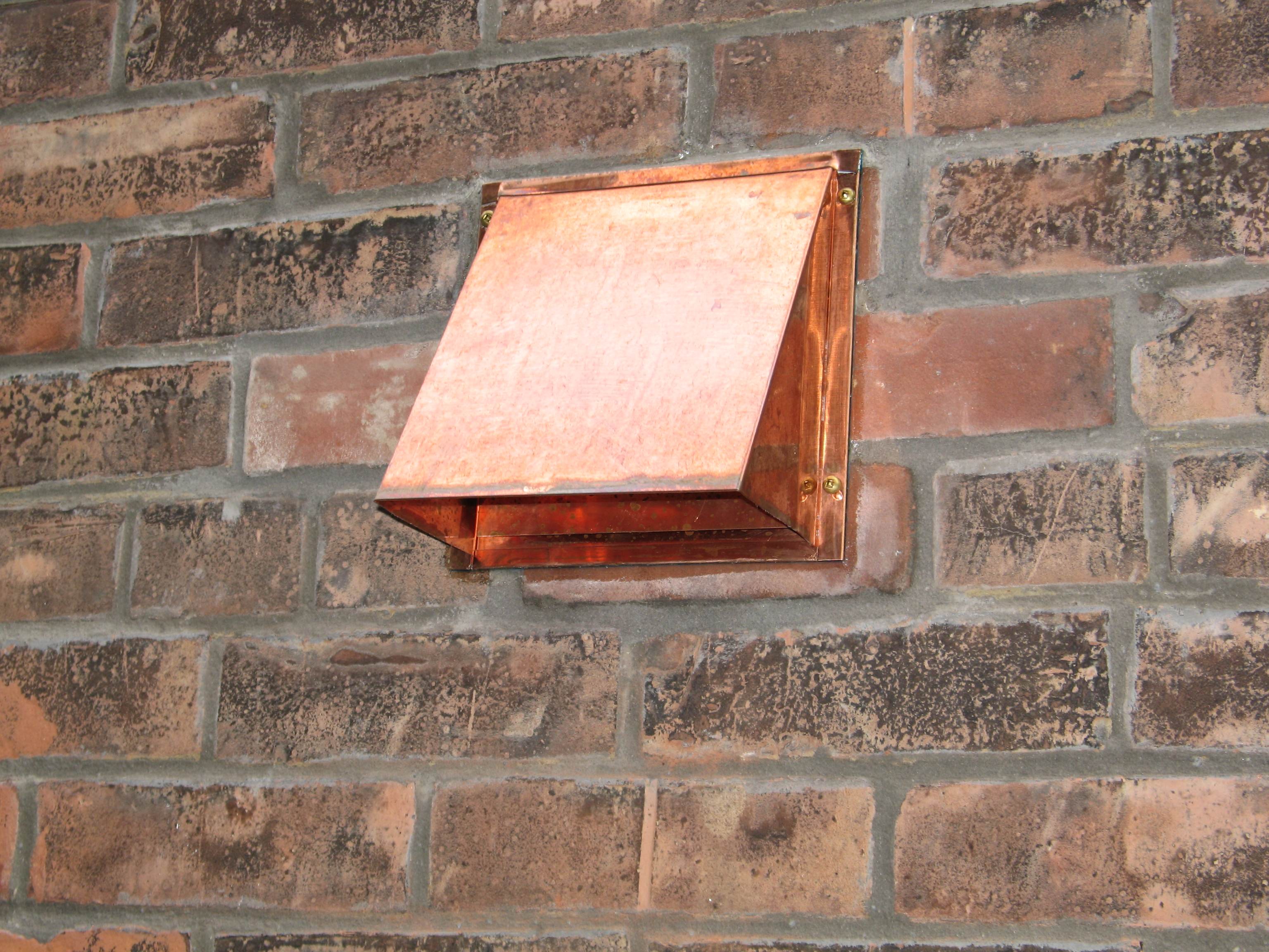 Copper Wall Vent Installed On Brick